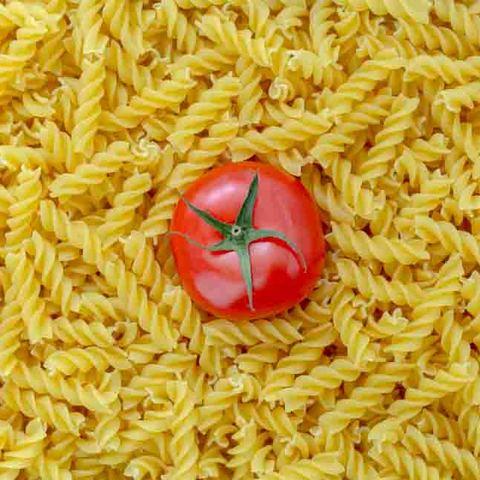 Tomato with fusilli pasta as background