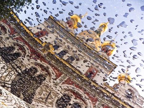 Russische Kirche spiegelt sich nach dem Regen in einer Motorhaube