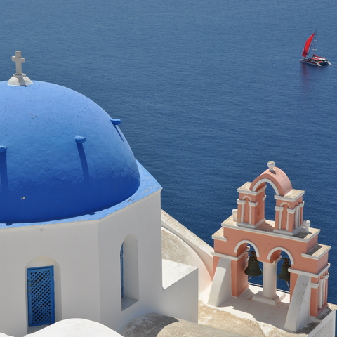 Katamaran mit rotem Segel vor Oia - Santorin